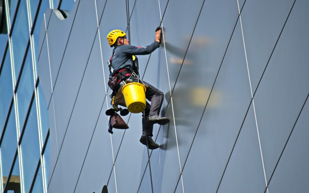 man-cleaning-the-glass-of-building