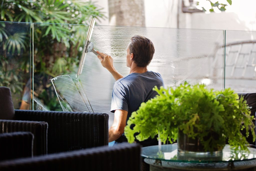 man-in-gray-shirt-cleaning-clear-glass-wall